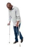Молодой человек при костыли пробуя погулять стоковые изображения rf
