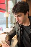 Молодой человек при мобильный телефон сидя в кафе и смотря на его p Стоковое фото RF