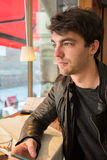 Молодой человек при мобильный телефон сидя в кафе и смотря снаружи Стоковые Фото