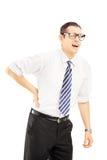 Молодой человек при связь страдая от боли в спине стоковые фото