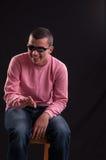 Молодой человек при солнечные очки сидя на стуле и смеяться над стоковое изображение