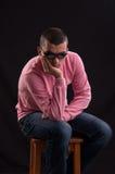 Молодой человек при солнечные очки сидя на стуле стоковое изображение
