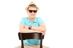 Молодой человек при солнечные очки сидя на стуле Стоковое фото RF