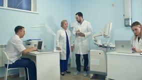 Молодой человек при таблетка имея взгляд вокруг медицинского офиса Стоковая Фотография