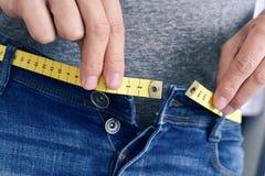 Молодой человек пробуя прикрепить его брюки Стоковое Фото