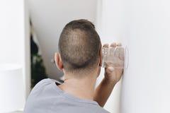 Молодой человек пробуя услышать через стену стоковые фотографии rf