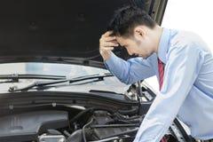 Молодой человек проверяя сломленный автомобиль машины Стоковая Фотография RF