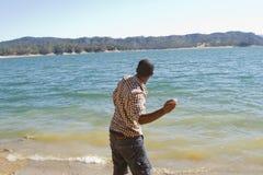 Молодой человек прыгает камни стоковая фотография rf