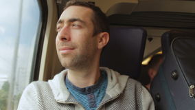 Молодой человек путешествуя на поезде и взглядах вне окно