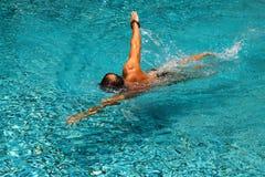 Молодой человек плавает в бассейне Стоковые Изображения