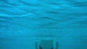 Молодой человек плавает под водой в бассейне видеоматериал