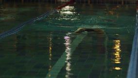Молодой человек плавая переднее ползание в бассейне Динамический и подходящий пловец дышая выполняющ ход бабочки видеоматериал