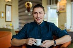 Молодой человек работая на компьтер-книжке в кафе Стоковые Фотографии RF