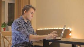 Молодой человек работая на компьтер-книжке дома видеоматериал