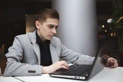 Молодой человек работая с компьтер-книжкой Стоковое Фото