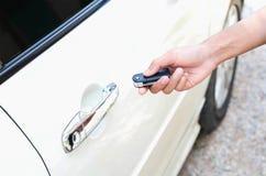 Молодой человек раскрывая его автомобильную дверь с remote управления Стоковое Изображение