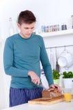 Молодой человек режа ломтик хлеба в его кухне Стоковая Фотография RF