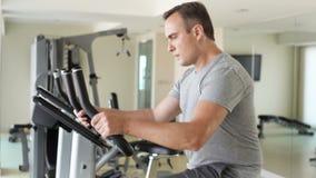 Молодой человек решительно красивой пригонки в серой футболке в спортзале делая тренировки на велотренажере видеоматериал