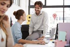 Молодой человек сидит на столе ` s женщины говоря в открытом офисе плана Стоковые Фото