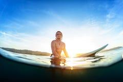 Молодой человек сидит на surfboard Стоковое Изображение RF