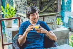 Молодой человек сидя в кафе выпивая очень вкусный чай имбиря утра в кафе Стоковые Изображения