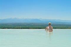 Молодой человек сидя в термальном бассейне с горным видом Стоковая Фотография