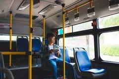 Молодой человек сидя в шине города и читая книгу Стоковые Фотографии RF