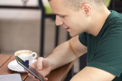 Молодой человек сидя и держа мобильный телефон в руке стоковые изображения rf