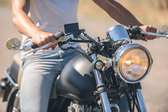 Молодой человек сидя на его мотоцилк Стоковое Фото