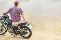 Молодой человек сидя на его мотоцилк стоковая фотография rf