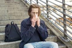 Молодой человек сидя на лестницах дуя его нос Стоковое Фото