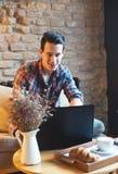 Молодой человек сидя на кафе, используя компьтер-книжку стоковая фотография