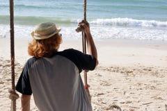 Молодой человек сидя на качании на пляже, чувствуя настолько унылый, один, сиротливом Стоковая Фотография RF