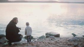 Молодой человек сидя на корточках на береге и разговаривая с мальчиком, чем стоит вверх время траты сынка отца совместно акции видеоматериалы