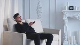 Молодой человек сидя на кресле используя дистанционное управление видеоматериал