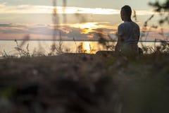 Молодой человек сидя на пляже и делая йогу Стоковое Изображение RF