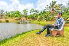 Молодой человек сидя на стуле Стоковое Фото
