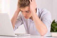Молодой человек сидя на таблице и используя компьтер-книжку Стоковые Фотографии RF