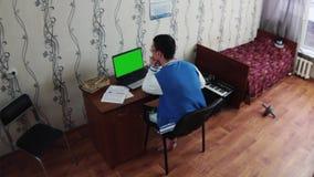 Молодой человек сидя на тетради в комнате спальни Старая кровать с красным одеялом синтезатор Студент видеоматериал