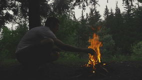 Молодой человек сидя около лагерного костера в лесе сток-видео