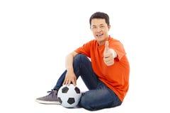 Молодой человек сидя с футболом и большим пальцем руки вверх стоковые изображения