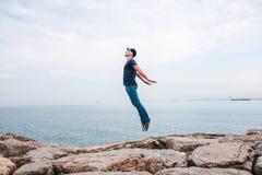 Молодой человек скача вверх портретирующ полет на фоне моря и неба концепция свободы жизнь Стоковое Изображение