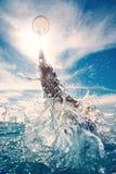 Молодой человек скача в воду Стоковые Изображения