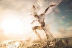 Молодой человек скача в море стоковые фото