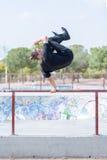 Молодой человек скача на поручни стоковое изображение
