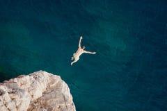 Молодой человек скача от скалы в море Стоковое Изображение RF