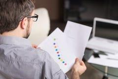 Молодой человек смотря бумагу в стеклах Стоковые Фотографии RF