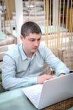 Молодой человек смотря в компьтер-книжке Стоковое Изображение
