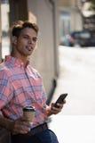 Молодой человек смотря отсутствующий пока полагающся на стене Стоковые Фото
