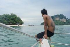 Молодой человек смотря туристскую шлюпку в Krabi, Таиланде стоковая фотография
